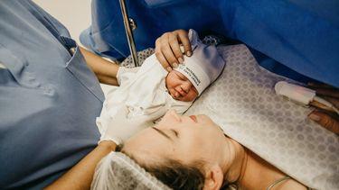 Moeder op de operatietafel die haar baby ontmoet na een keizersnede