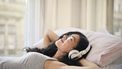 Vrouw met koptelefoon op in bed die naar een luisterboek luistert