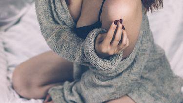 Vrouw waarbij haar vest van haar schouder is gegleden en je een stukje van haar lingerie ziet