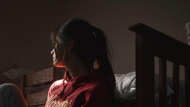 Vrouw die naar buiten staart en klaar is met het rotjaar