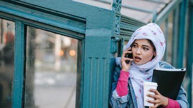 Vrouw die zich niet veilig voelt op straat en doet alsof ze belt om het hoekje