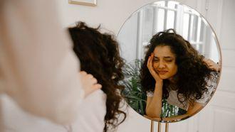 relatie / vrouw kijkt twijfelend in de spiegel