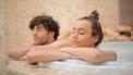 Vrouw en man liggen ontspannen in een hot tub, en doen deze herkenbare dingen in een spa