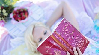 Vrouw ligt op haar rug en leest een boek. Levenslessen van Rumi