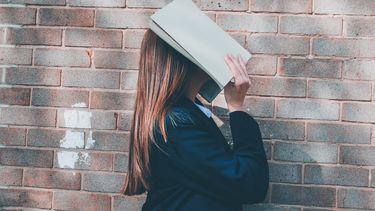 meisje verbergt emoties met een boek voor haar gezicht