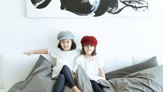 Twee kinderen zitten op bed- deze positie kunnen kinderen beter niet aannamen