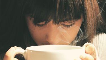 Vrouw drinkt van een grote witte mok en ervaart de voordelen van muntthee