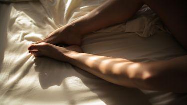 vrouw ligt met benen wijd op bed