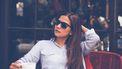 vrouw met zonnebril op terras. alpha vrouw kenmerken