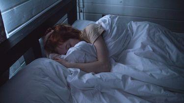 Vrouw die 's nachts wakker wordt in bed