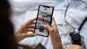 vrouw houdt telefoon met apps voor ouders vast