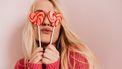 Vrouw die twee hartjes lolly's voor haar ogen houdt omdat die haar als Valentijnscadeau zijn gegeven