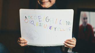 alfabet op een blaadje geschreven door een jongetje