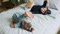 Jonge moeder met haar dochter die op bed spelen