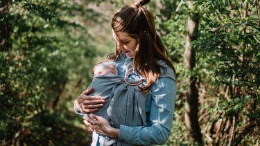Moeder met haar pasgeboren baby in een draagdoek