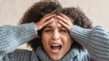 Vrouw met handen in het haar en denkt aan vieze dingen die vrouwen deden tijdens menstruatie