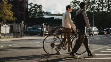 Twee tieners die over straat lopen met een fiets