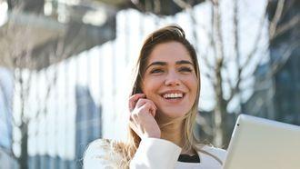 lachende vrouw met telefoon en tablet. Perfecte tijd voor carrière switch