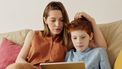 Moeder die met haar zoon praat over het nieuws dat hij op zijn tablet ziet