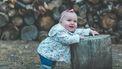 Baby die tegen een houten blok staat en leert lopen zonder babyschoentjes