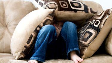 Kind dat verdrietig onder de kussens van de bank schuilt