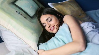 Vrouw slaapt met een lach op haar gezicht en ervaart waarom slapen zo gezond is