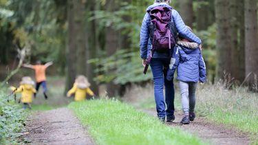 gezin is aan het wandelen in het bos