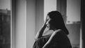 Vrouw die verdrietig uit het raam kijkt en denkt aan har doodgeboren zoontje