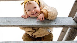 Kindje dat in november is geboren en buiten op een trapje speelt
