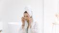 Vrouw in witte badjas en handdoek op haar hoofd brengt zalf aan op haar gezicht. Skincare in de koelkast