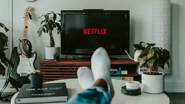 Netflix op een beeldscherm en iemand ligt op de bank