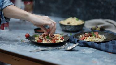 Een bord pasta dat iemand met handen gaat eten