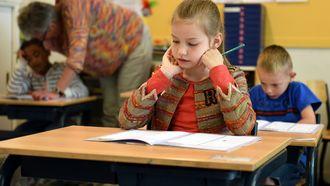 Meisje dat op school zit in de klas