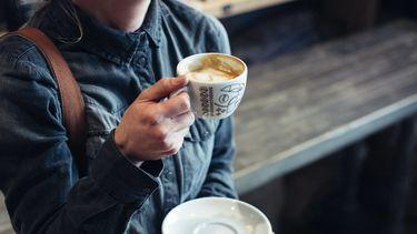 vrouw met cappuccino in haar hand