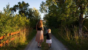 moeder en dochter lopen door de groene natuur