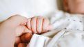 Iemand houdt handje van baby vast. Zeldzame babynamen