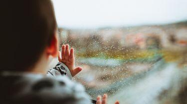 Kind dat naar buiten kijkt waar het regent