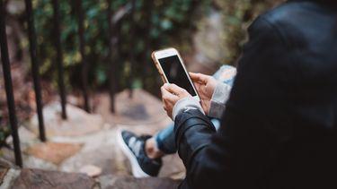 vrouw zit op haar smartphone