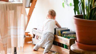 kindje kijkt in een kist met speelgoed