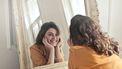 Vrouw in gele jurk kijkt lachend in de spiegel, en weet hoe ze van haar eigen lichaam moet houden