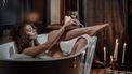 Vrouw die probeert haar benen glad te scheren in bad