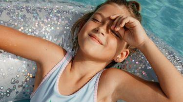 leeftijd van 9 / meisje ligt in zwembad