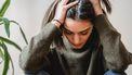 Vrouw met handen in het haar kan niet stoppen met piekeren