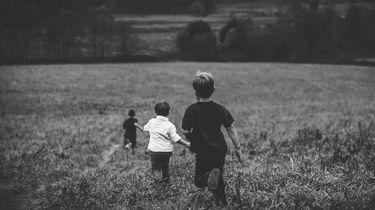 gezin met eerste, tweede en derde kind, rennen door een veld