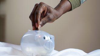 Vrouw die geld in plastic spaarvarken doet