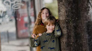 Broer en zus bij een boom wiens relatie nog zal veranderen met de jaren