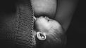 Zwart wit foto van baby die borstvoeding krijgt, waarschijnlijk nachtvoeding