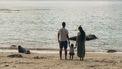 Gezin dat samen de wereld over reist en nu op een strand staat kijkend naar de zee
