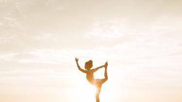 Een vrouw die fertility yoga doet en op 1 been staat tegenover de zonsondergang