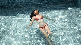 vrouw ligt in een zwembad met een geschoren lichaam zonder bultjes